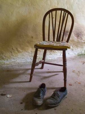 empty chair with man's old shoes in a stone room.