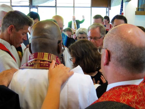 Kelli in the midst of the clergy laying hands.