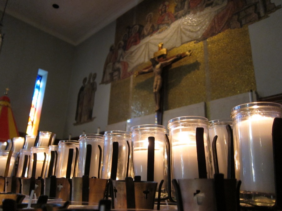 votive candles in the foreground with christ on the cross on the wall in the background; taken at historical basilaca